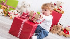 Curious child: young girl opening Christmas present with teddy bears in background