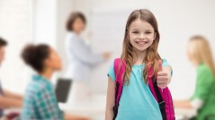 education, gesture and school concept - happy and smiling little girl with school bag showing thumbs up